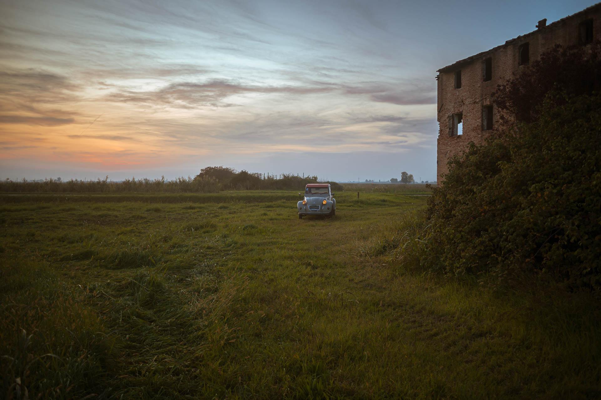 tramonto con citroen 2cv e casa agricola abbandonata